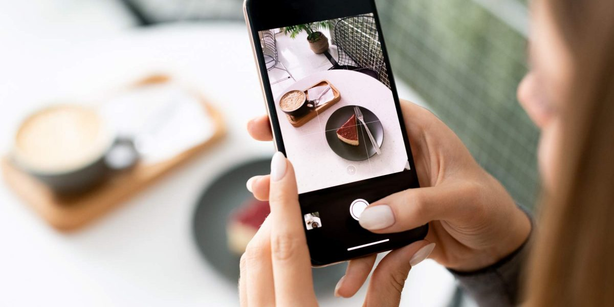 Young woman holding smartphone over served table in cafe while taking photo of cappuccino and dessert